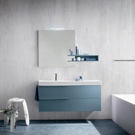 Mobile da bagno sospeso in finitura azzurro, con maniglie metalliche a lama e specchiera con mensola.