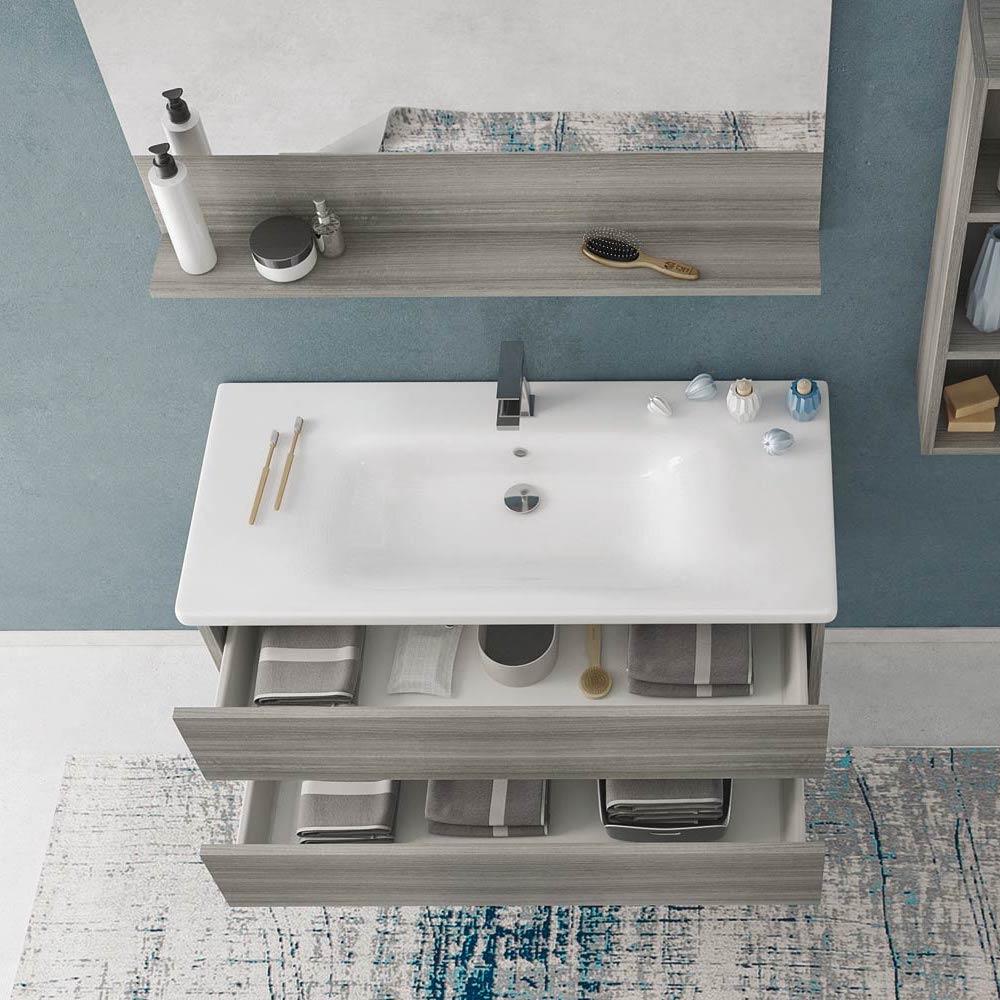 Mobile da bagno con lavabo in ceramica e cassetti aperti. Specchiera con mensola
